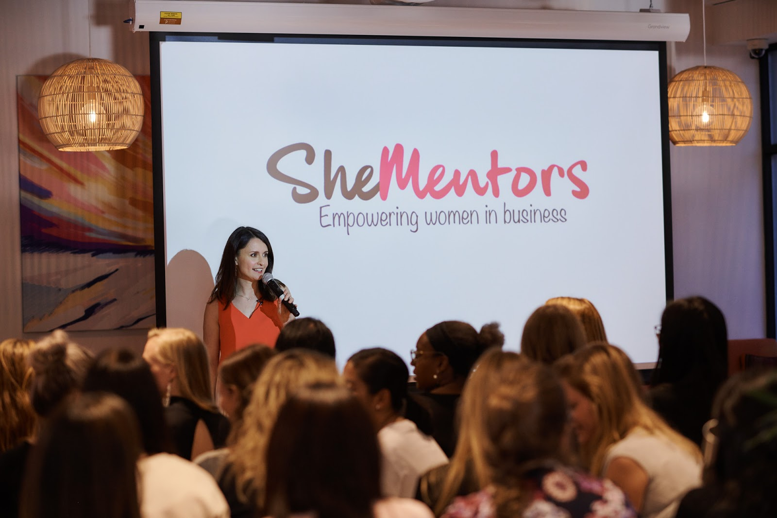 Women watch She Mentor's presentation